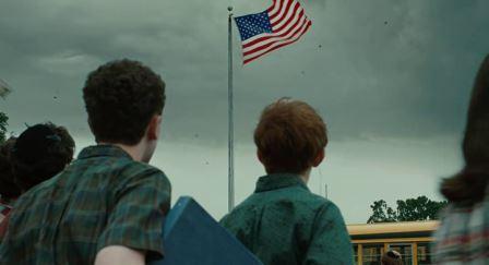 Scena di A Serious Man. Una bandiera degli Stati Uniti sta per essere strappata dall'asta da un imminente uragano.