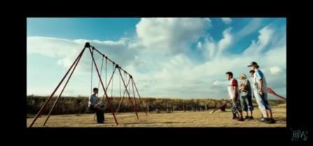 Harry potter seduto su un'altalena viene infastidito da suo cugino e altri tre ragazzi.